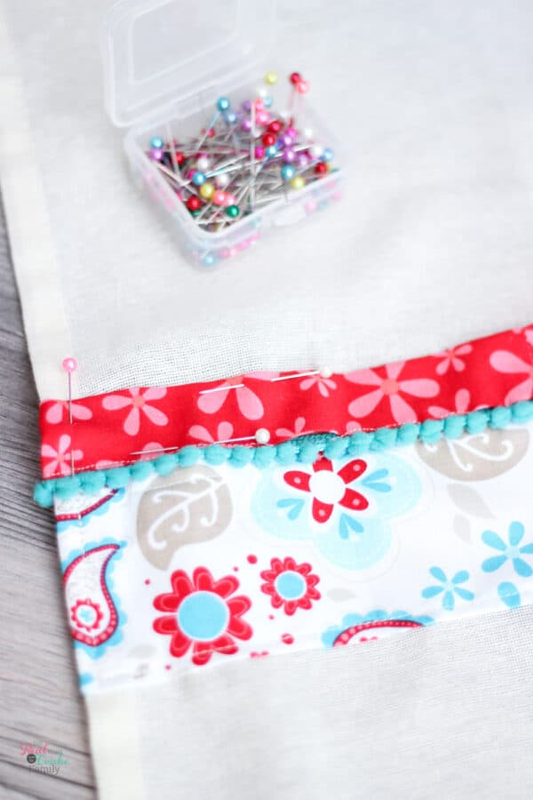 pinning 2nd strip of fabric with pom poms above first strip