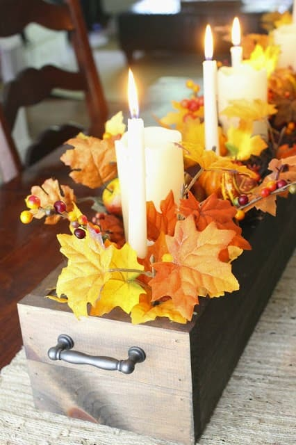 centerpiece in a box with fall leaves and candles