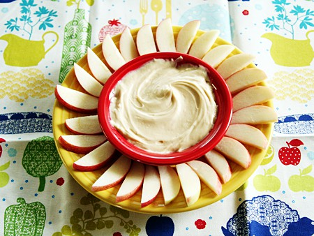 tray of apples slice with bowl of dip in middle