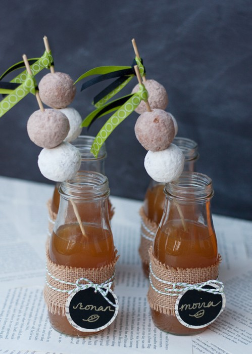 donuts on straws in glass of apple cider