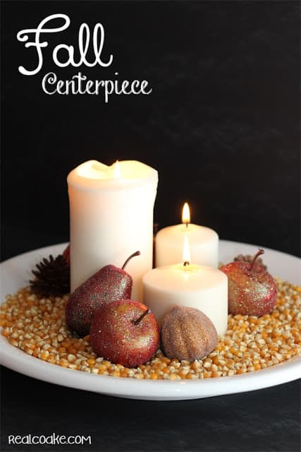 fall centerpiece using candles, popcorn, and plastic fall fruit