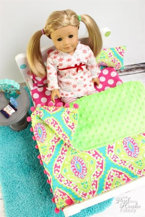 These doll bed comforters are so adorable! I love sewing cute things for our American Girl Dolls. The pom pom trim just makes these so cute!