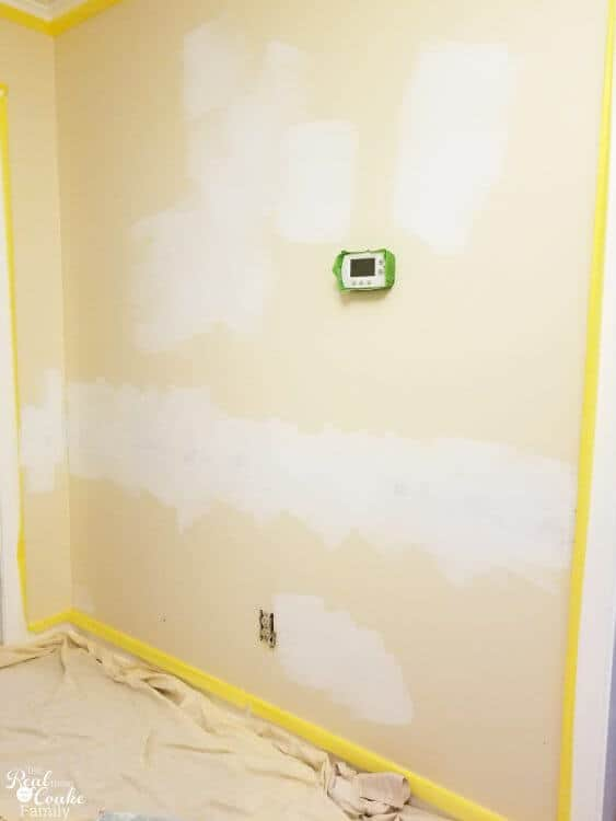 picture of wall with primer painted on area where chair rail was