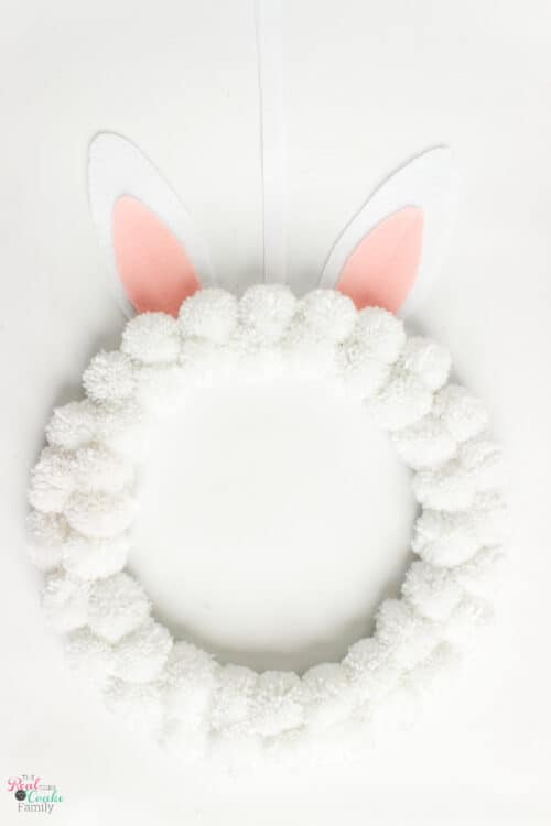 Make this cute DIY Bunny Easter Wreath! It's an easy Easter craft that uses pom poms and makes cute decorations for your home.