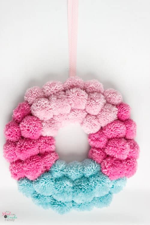 Cute DIY pom pom wreath tutorial showing step by step how to make this easy wreath using a pom pom maker. Perfect pom pom crafts for your home decor.