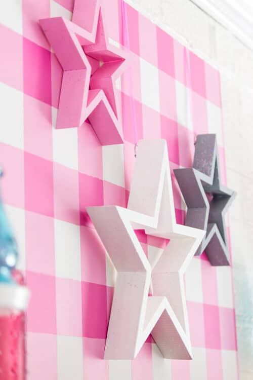 side view of pink, white, and gray stars on pink gingham background