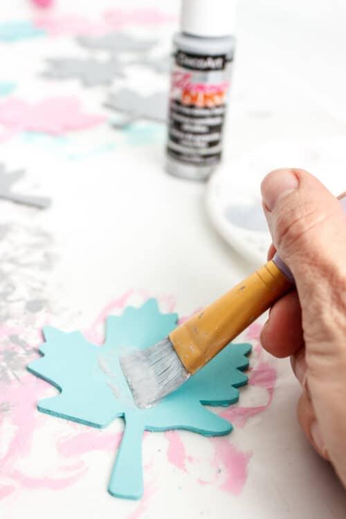 painting glitter paint on blue wood leaf