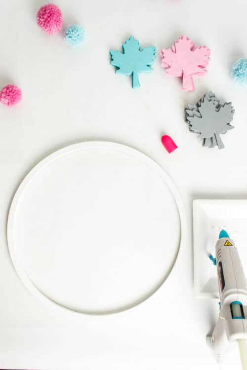 white wreath hoop with pink, blue and gray leaves and hot glue