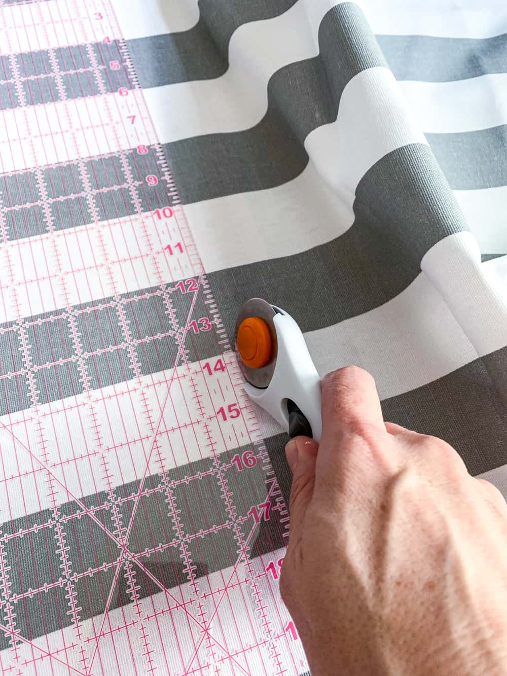 cutting grey and white striped fabric