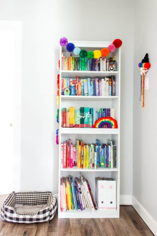 grey painted hallway with white bookshelf with rainbow decorations