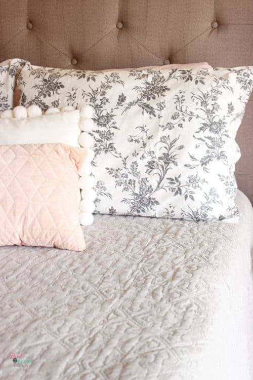 shortened pillow sham on bed with 2 decorative pillows