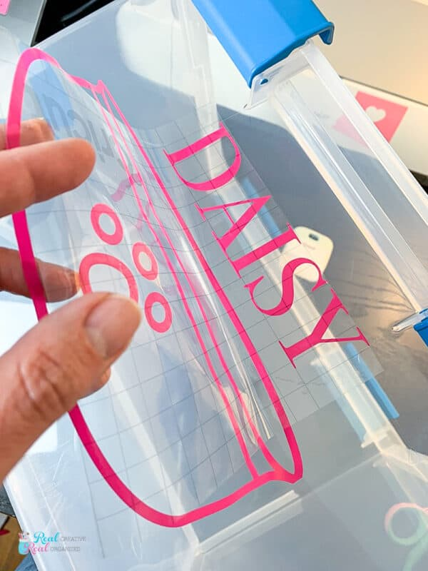 placing cut adhesive vinyl on storage bins