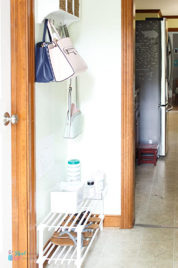 Entry hallway with shoe rack with supplies on top for sanitizing station